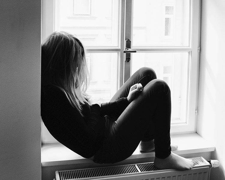 a sad young girl is looking out of a window
