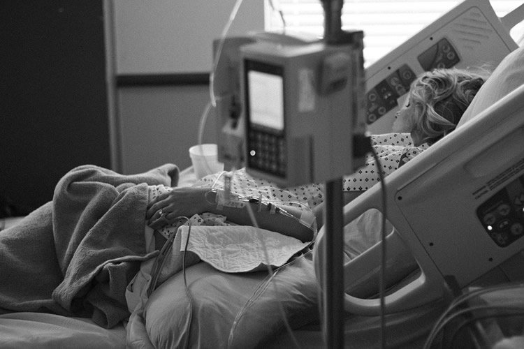 This shows a woman laying in a hospital bed with an IV drip