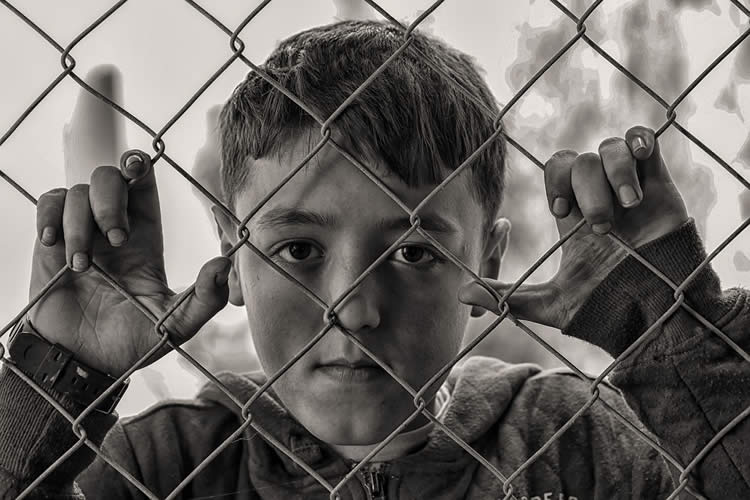 This shows a hungry looking boy looking through a wire fence