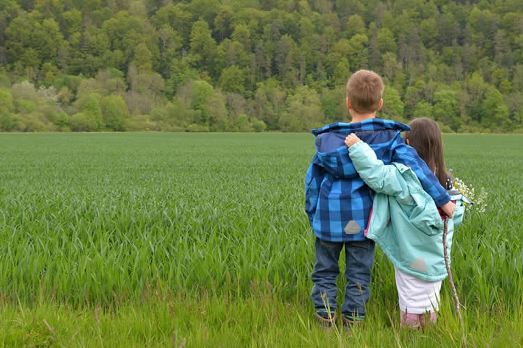 This shows a boy and girl walking in a field