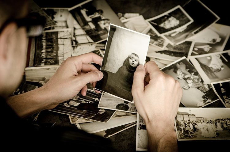 This shows a man looking at old photos
