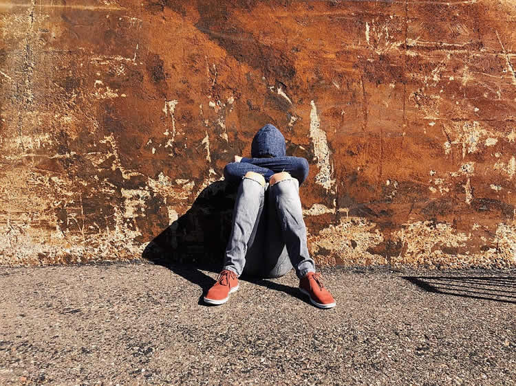 This shows a teen sitting against a wall