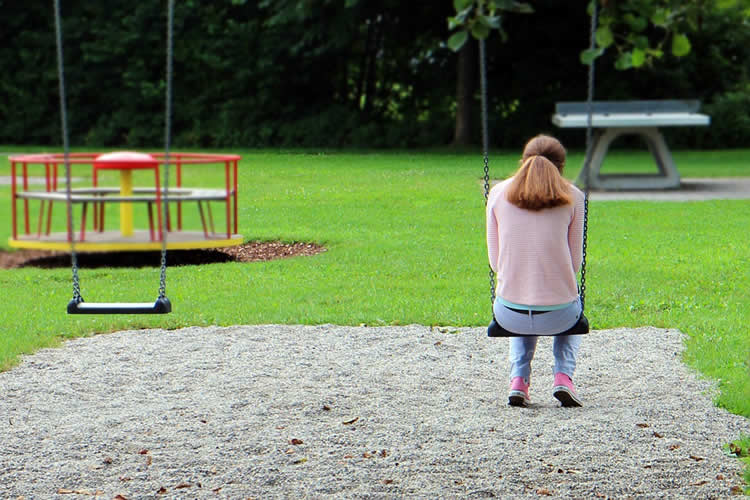 This shows a teenaged girl sitting alone on a swing in a park