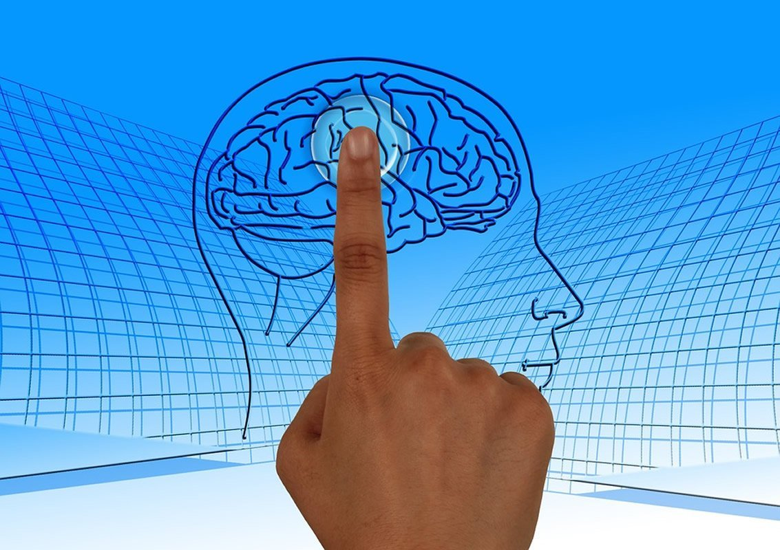 This shows someone pressing a button on a brain drawing