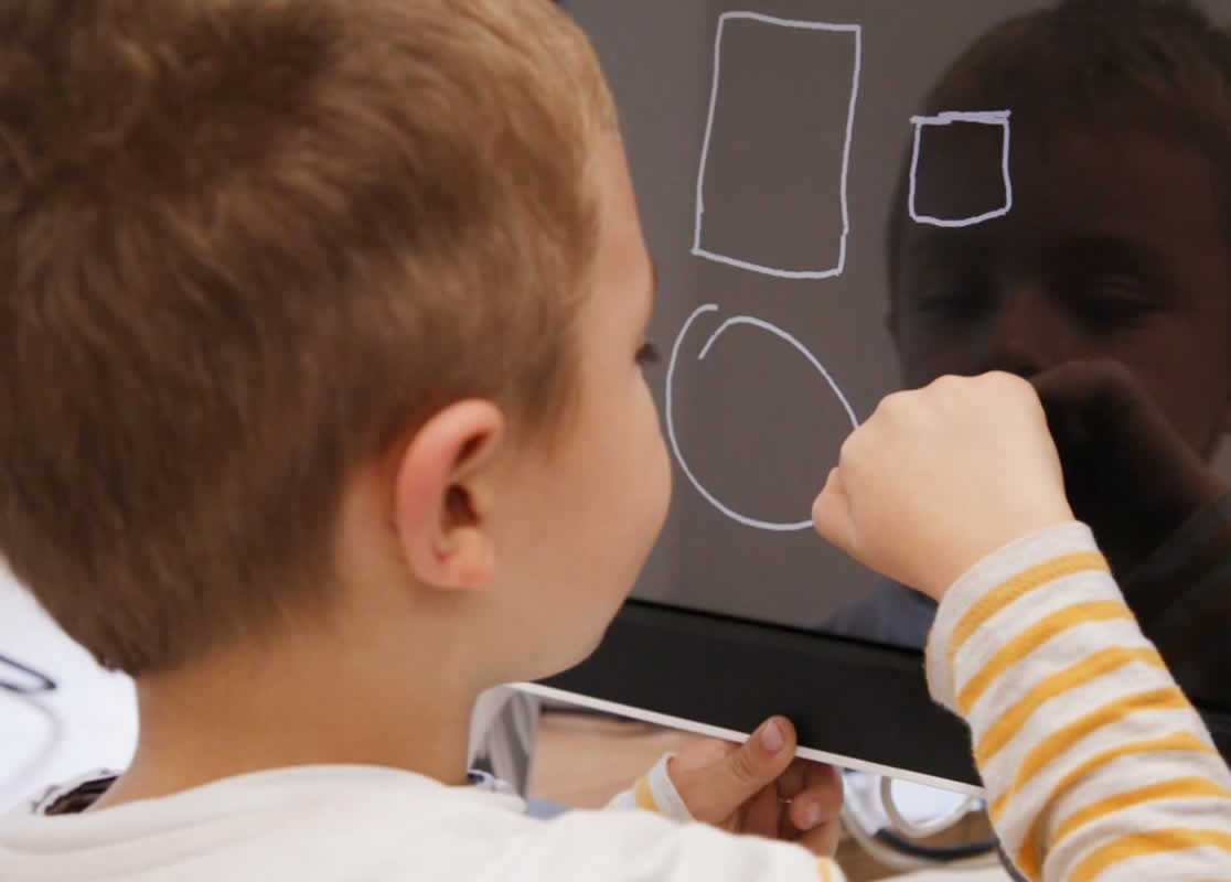 This shows a child drawing shapes on a blackboard