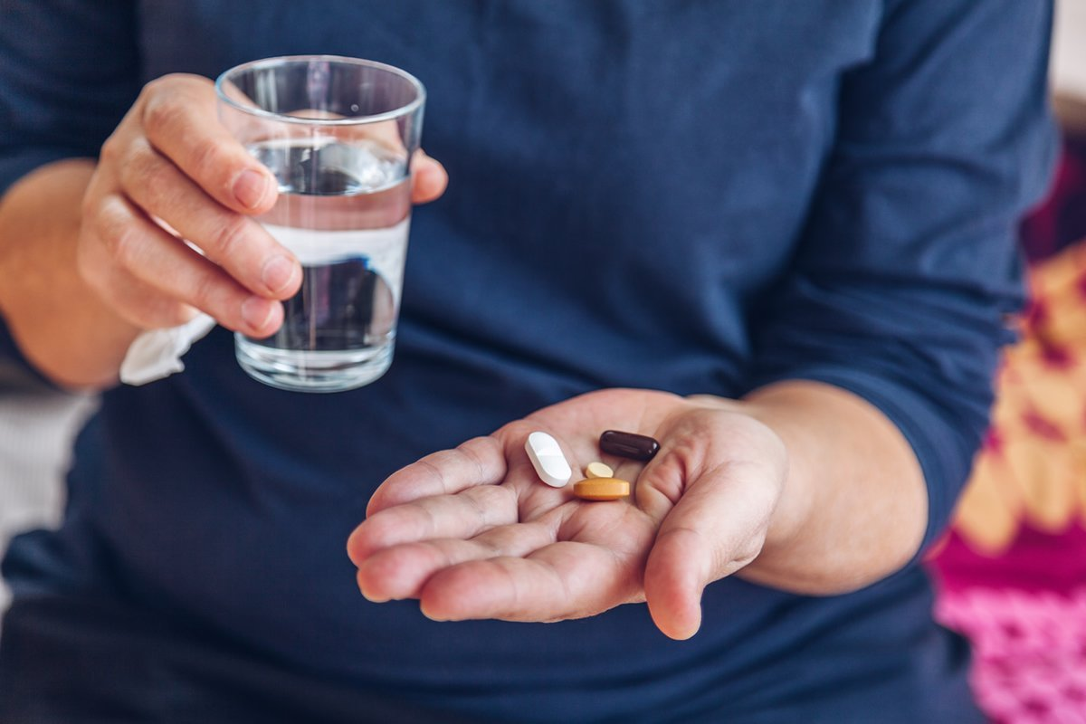 This shows a person with pills in their hands