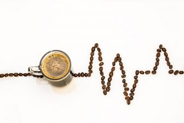 This shows a cup of coffee and coffee beans made to look like a heart rhythm line