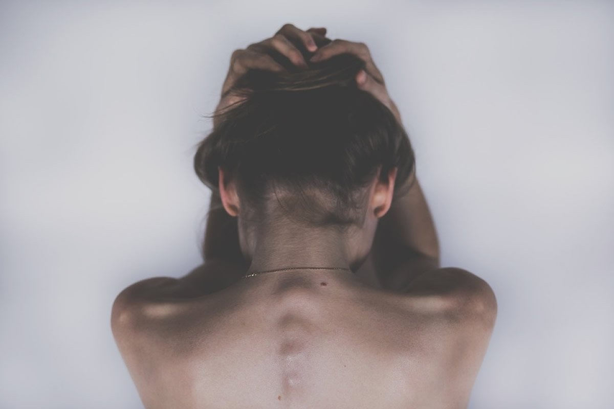 This shows a woman holding her head