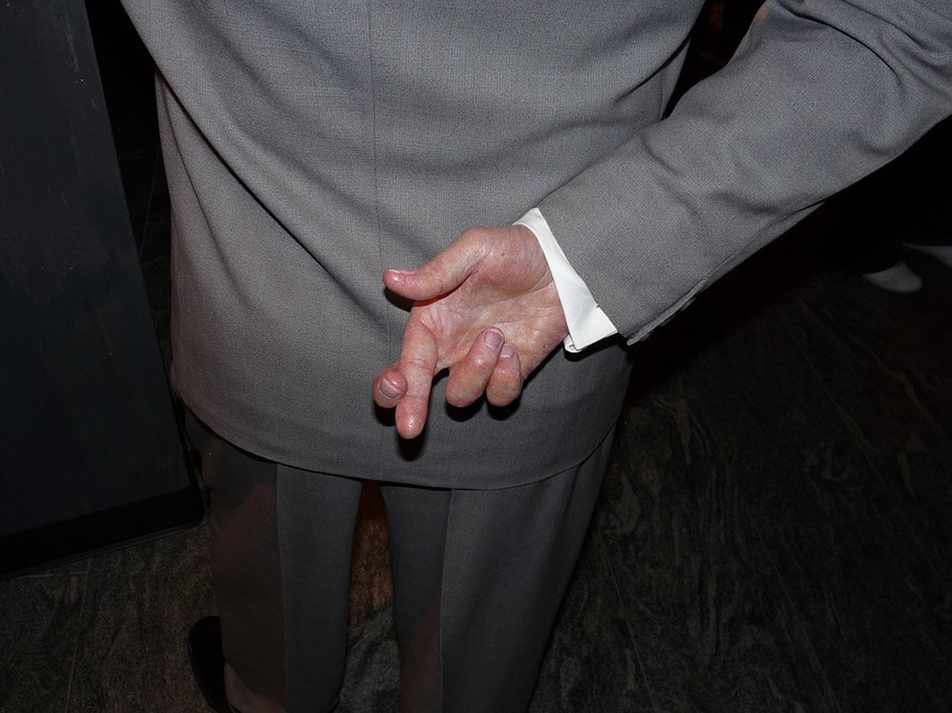 This shows a man in a business suit, crossing his fingers behind his back