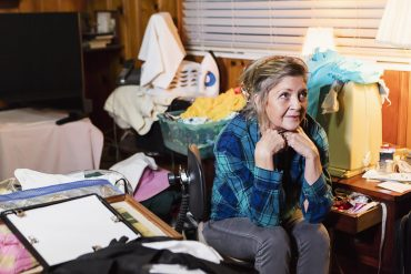 This shows a woman surrounded by clutter