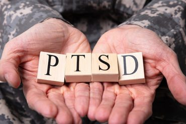 This shows someone with PTSD made from scrabble letters in their hands