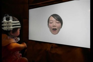 This shows a baby looking at a picture of a woman yawning