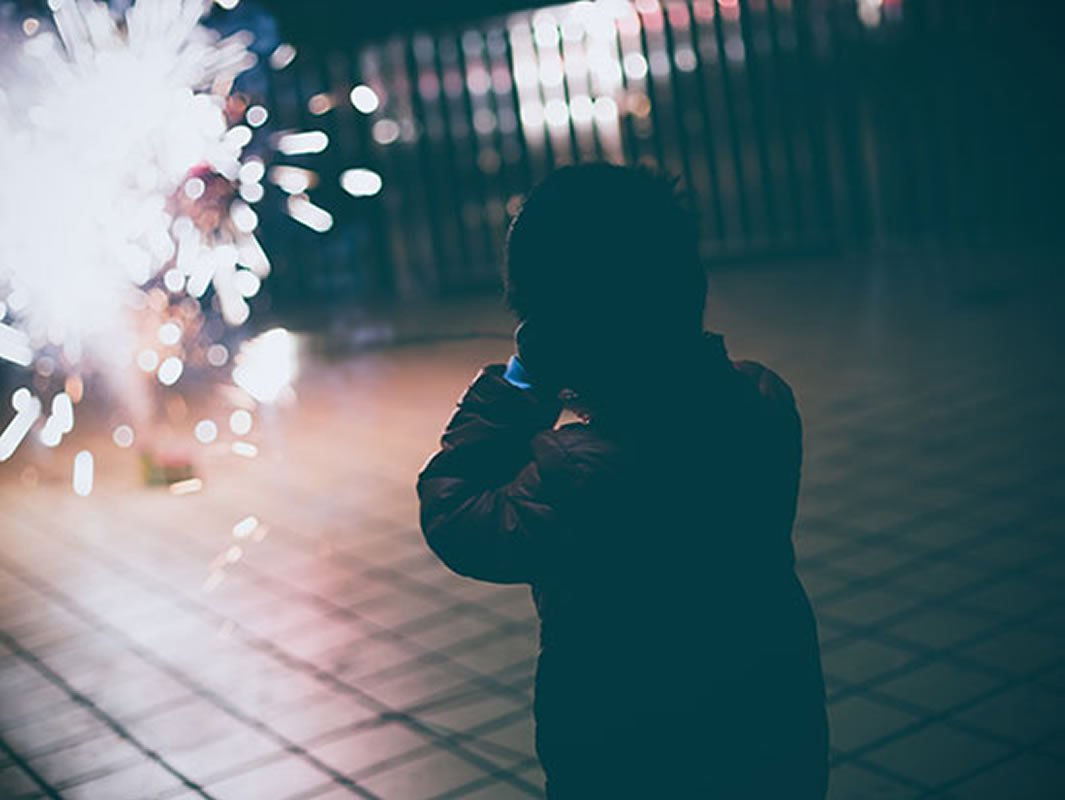 This shows a child covering their ears at fireworks
