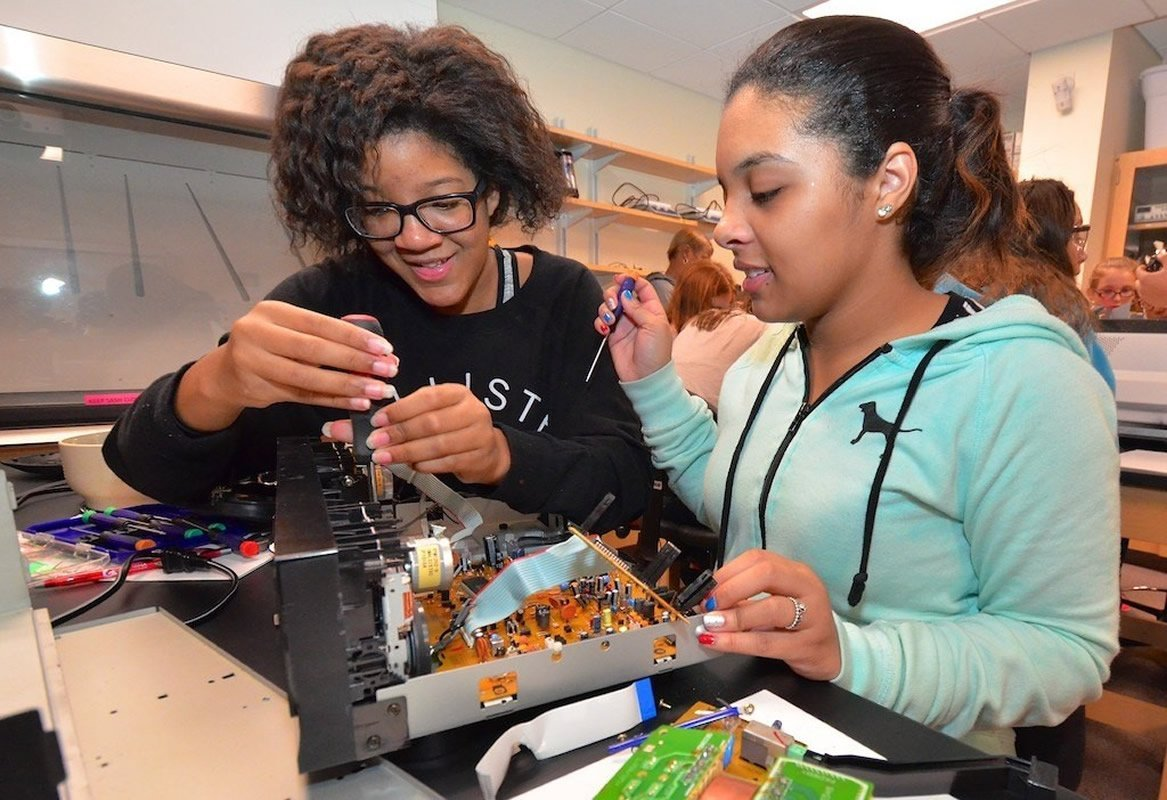 This shows two girls working with circuit boards
