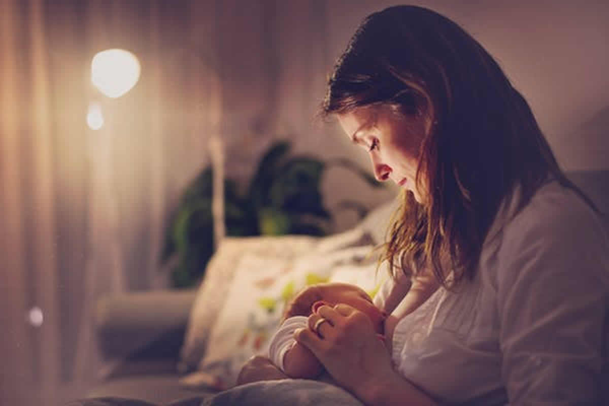 This shows a mom breastfeeding her newborn at night