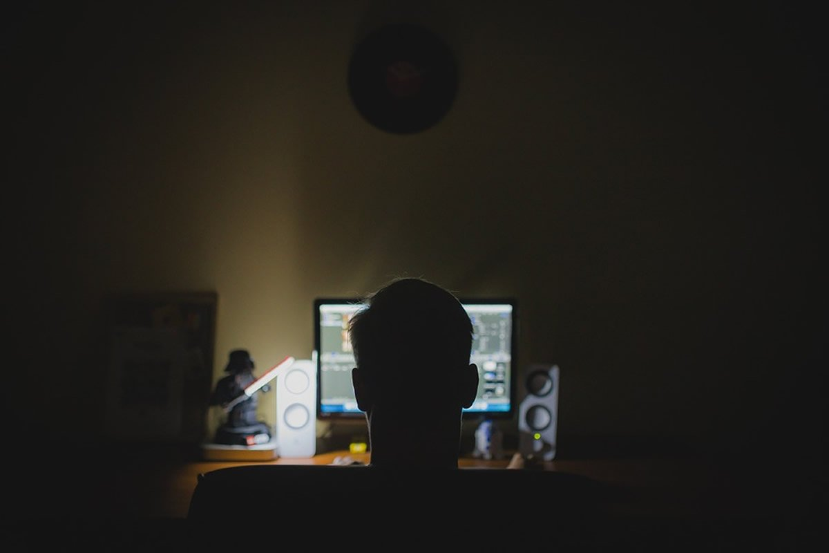 This shows a person in front of a computer at night