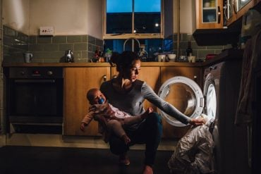 This shows an exhausted mom with a baby loading a washing machine