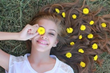 This shows a teenage girl with flowers in her hair
