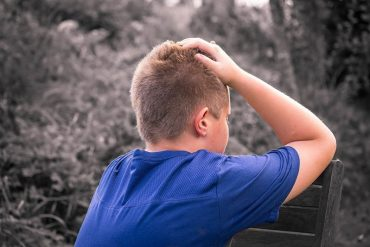 This shows a young boy holding his head