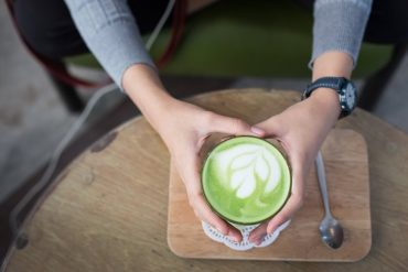 This shows a woman holding a cup of green tea