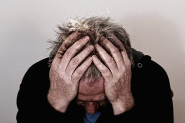 This shows an older man holding his head