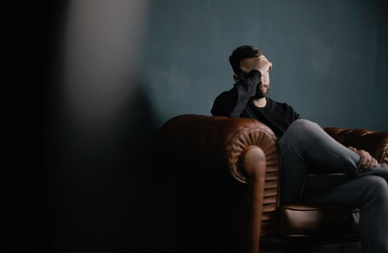 This shows a man sitting on a sofa holding his head