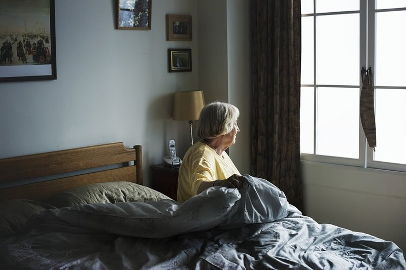 This shows an older lady sitting on a bed