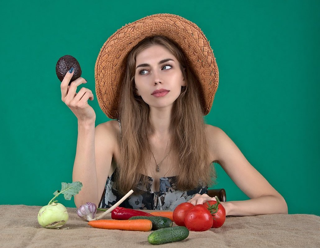 This shows a woman holding up veggies