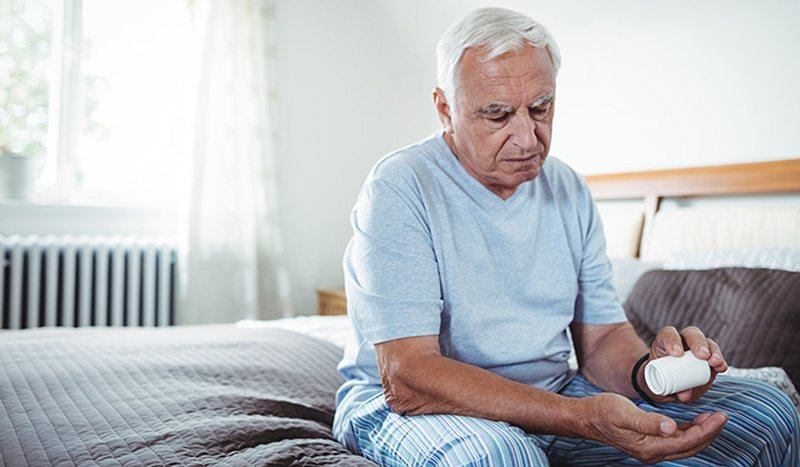 This shows an older man opening a bottle of pills