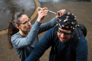 This shows the researcher placing an EEG cap on a test subject