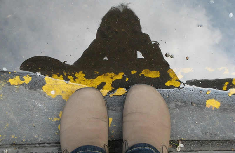 This shows a person's shoes and reflection in a puddle