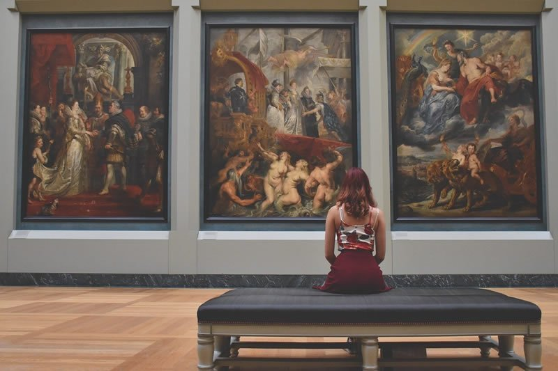 This shows a woman looking at paintings in a gallery