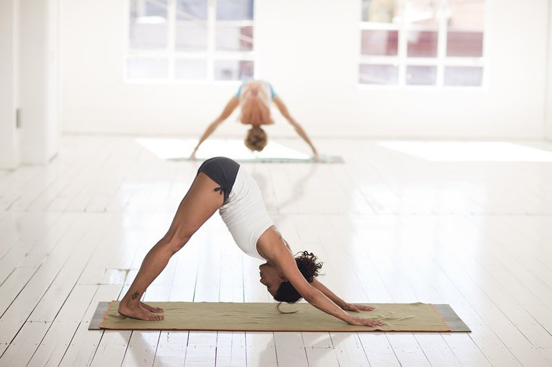 This shows a woman in the downward dog yoga pose