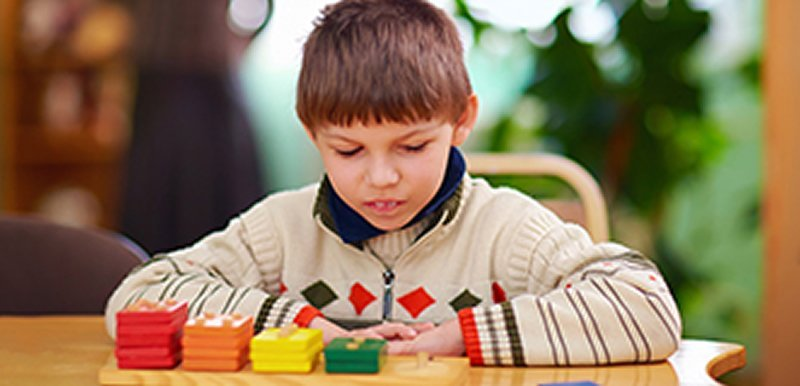 This shows a little boy playing with blocks