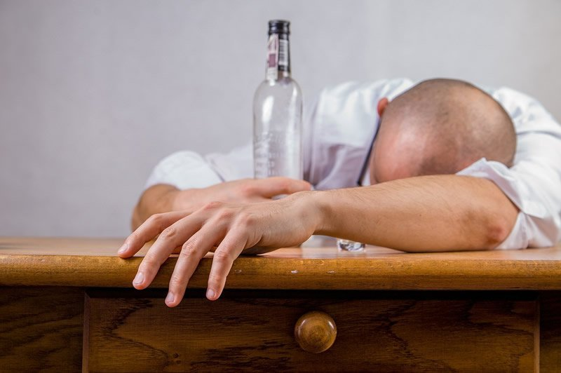 This shows a person laying with their head on the table and an empty alcohol bottle