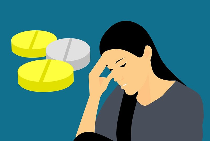 This is a cartoon of a woman holding her head and pills