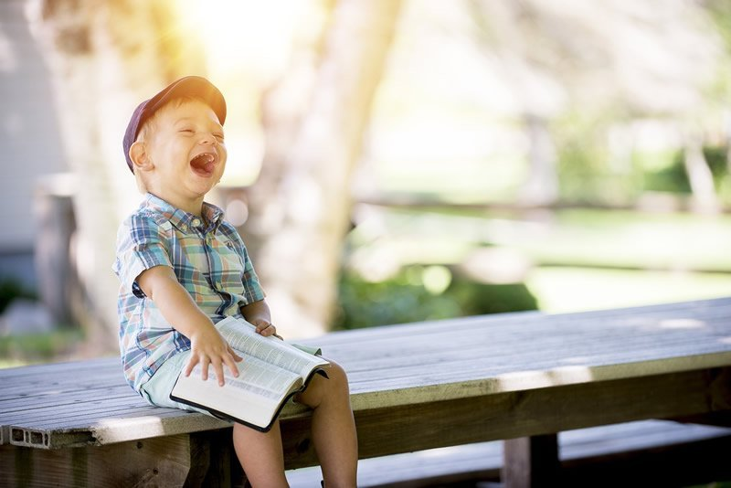 This shows a happy little boy reading outdoors