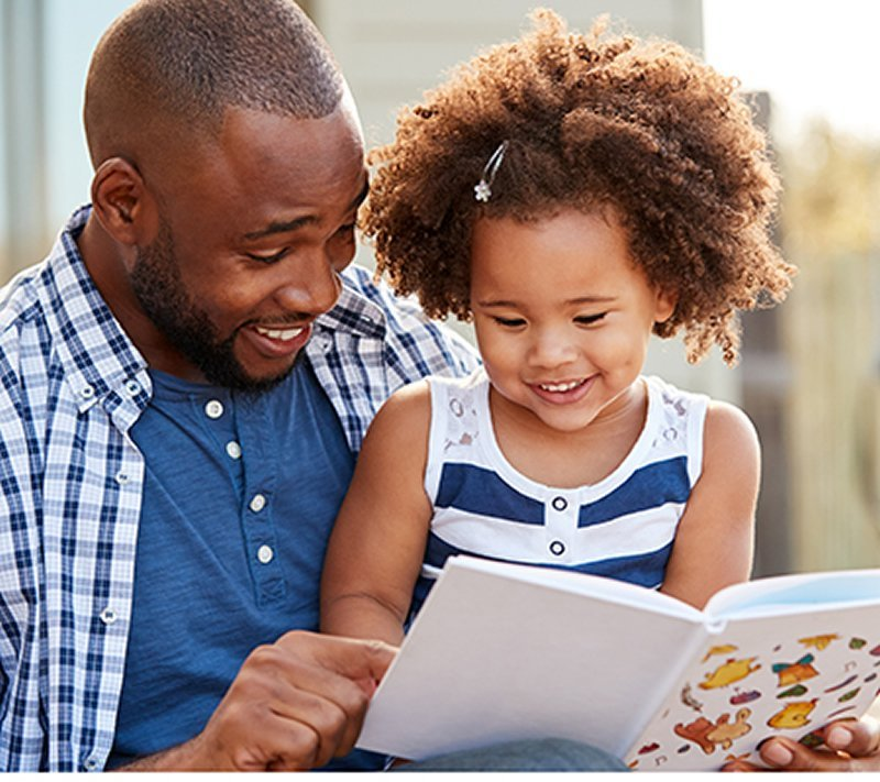 This shows a dad reading to his daughter