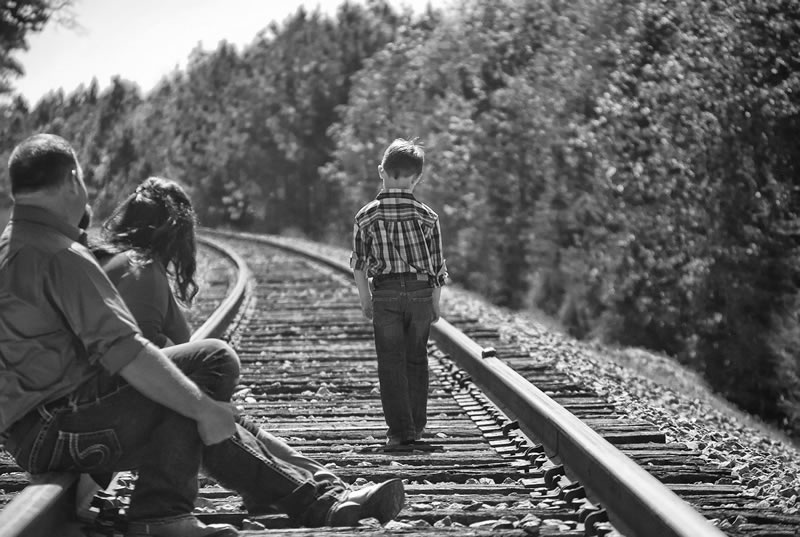This shows a cihld walking on a train track