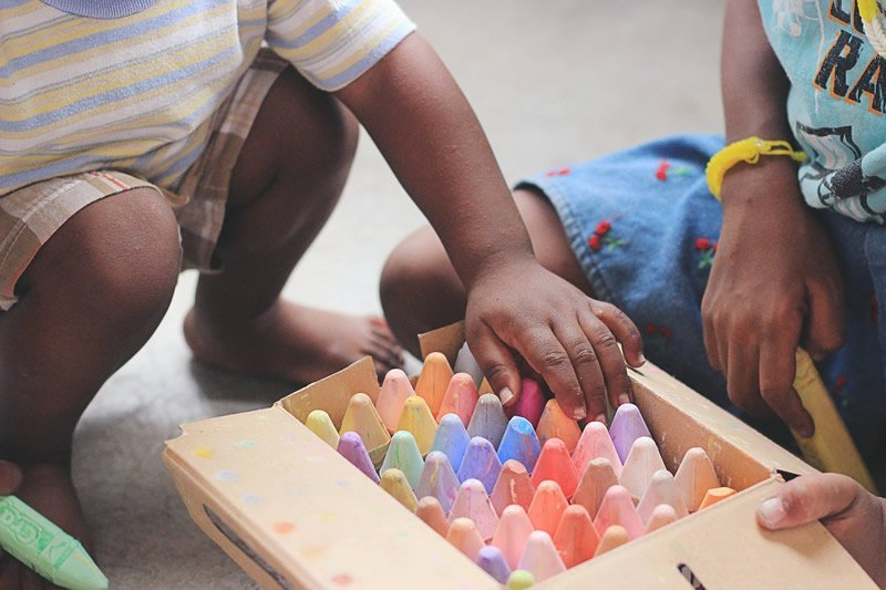 This shows children drawing with chalk