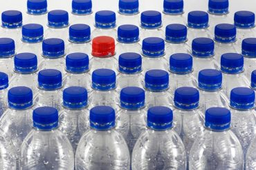 This shows a lot of plastic bottles with blue lids and one with a red lid
