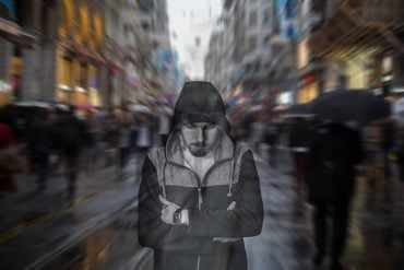 This shows a lonely man on a crowded street