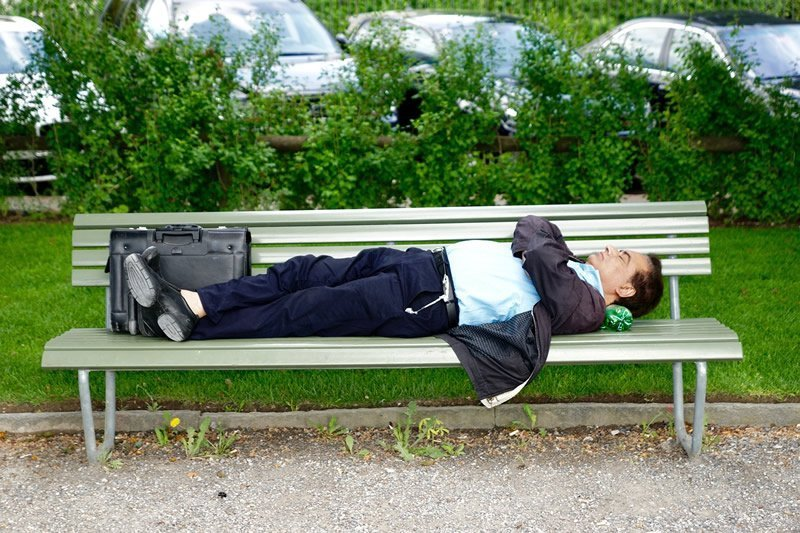 This shows a man sleeping on a park bench