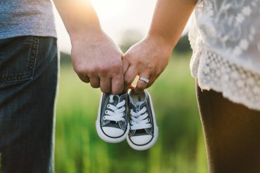 This shows a couple holding baby shoes