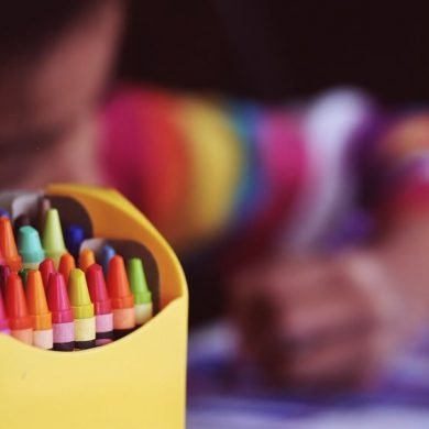 This shows a child coloring with crayons