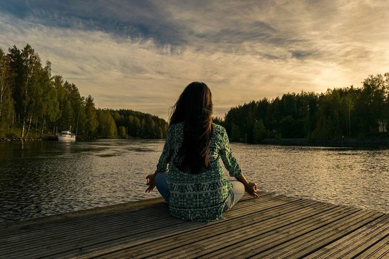 This shows a woman meditating next to a river