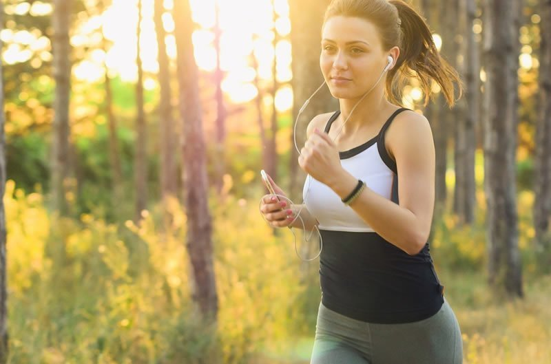 This shows a woman running while listening to music on headphones
