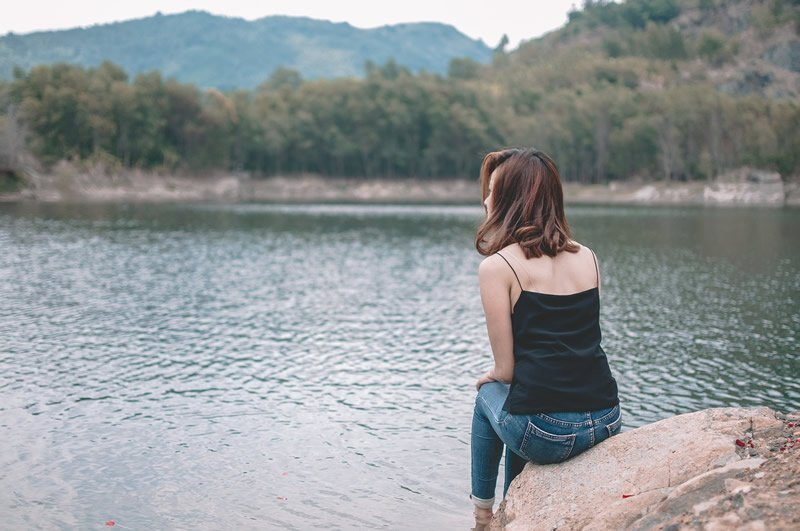 This shows a woman sitting by a lake
