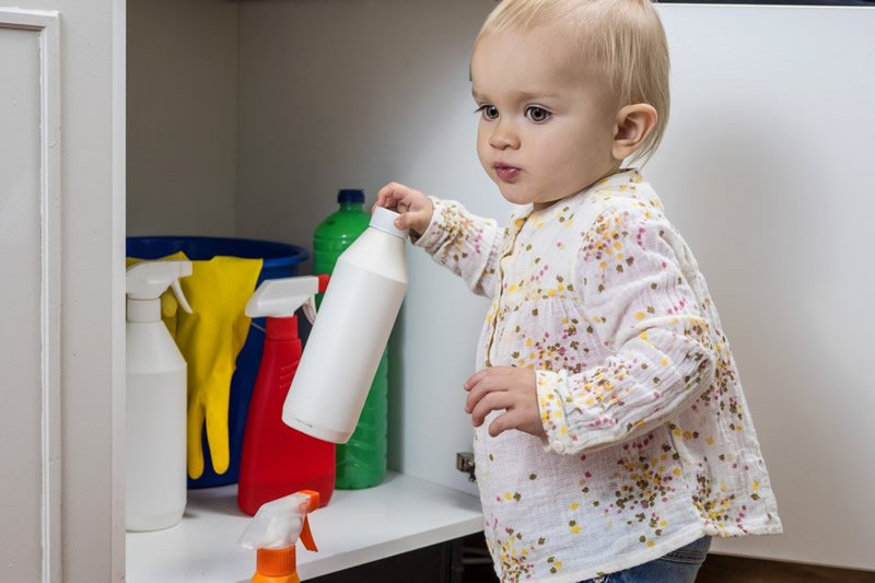 This shows a young girl with cleaning products in her hand