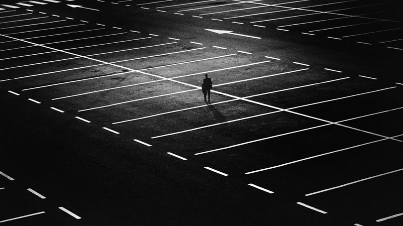 This shows a man in an empty parking lot